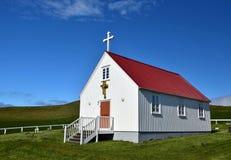 Una pequeña iglesia blanca en Islandia con un tejado rojo foto de archivo libre de regalías