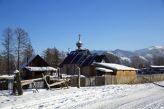 Una pequeña iglesia en el pueblo ruso Zamulta en invierno en el valle de Uimon, montañas de Altai Fotografía de archivo
