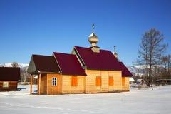 Una pequeña iglesia en el pueblo ruso Zamulta en invierno en el valle de Uimon, montañas de Altai Fotos de archivo