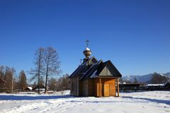 Una pequeña iglesia en el pueblo ruso Zamulta en invierno en el valle de Uimon, montañas de Altai Imagen de archivo libre de regalías