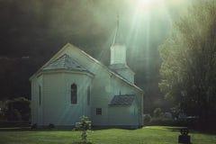 Una pequeña iglesia protestante noruega blanca en el sol foto de archivo