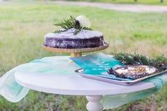 Una pequeña mesa redonda para un partido amistoso en el césped En un mantel del satén hay dulces fotografía de archivo libre de regalías