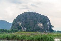 Una pequeña montaña escarpada en el medio del campo verde Imagenes de archivo