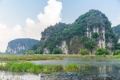 Una pequeña montaña escarpada en el medio del campo verde Fotos de archivo