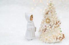 Una peque?a mu?eca en ropa del invierno est? mirando el ?rbol del A?o Nuevo ?rbol de navidad con las perlas y el fondo hermoso de imagen de archivo