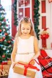 Una pequeña muchacha abre una caja de regalo Año Nuevo del concepto, Feliz Navidad Foto de archivo