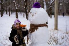 Una pequeña muchacha alegre sostiene una zanahoria grande, la nariz de un muñeco de nieve grande Imagen de archivo