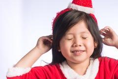 Una pequeña muchacha asiática linda en el vestido de Santa Cross en el aislante b blanco Fotografía de archivo libre de regalías