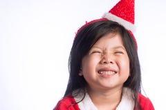 Una pequeña muchacha asiática linda en el vestido de Santa Cross en el backgroun blanco Fotos de archivo libres de regalías