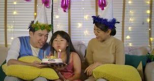 Una pequeña muchacha asiática linda que celebra su cumpleaños con una torta y una familia feliz metrajes