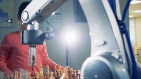 Una pequeña muchacha cabelluda oscura está jugando a ajedrez con un brazo robótico