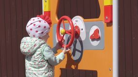 Una pequeña muchacha caucásica hermosa juegos de 3 años en un patio nuevo y multicolor moderno en un día de primavera almacen de video