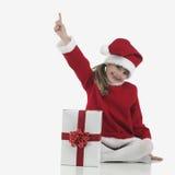 Una pequeña muchacha de Papá Noel que indica Foto de archivo libre de regalías
