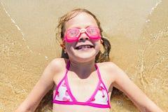 Una pequeña muchacha divertida está mintiendo en una playa arenosa en ella detrás - ella está riendo y lleva gafas que nadan fotografía de archivo libre de regalías