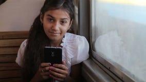 Una pequeña muchacha gitana que usa un smartphone en el tren almacen de metraje de vídeo
