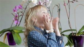 Una pequeña muchacha hermosa en un vestido azul está corrigiendo su pelo rizado rubio almacen de metraje de vídeo