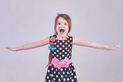 Una pequeña muchacha hermosa grita, lanzando sus manos en los lados imagen de archivo