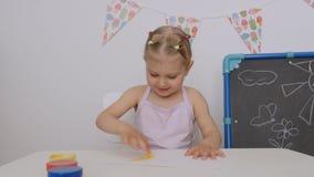 Una pequeña muchacha linda que se sienta en la tabla dibuja en el papel con las pinturas brillantes del finger, sumergiendo sus f almacen de metraje de vídeo