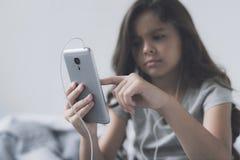 Una pequeña muchacha negro-cabelluda en los auriculares blancos con un smartphone gris en sus manos cambia música Foto de archivo