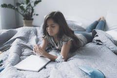 Una pequeña muchacha negro-cabelluda miente en una cama en los auriculares blancos, escucha la música, mira un cuaderno blanco y  Foto de archivo