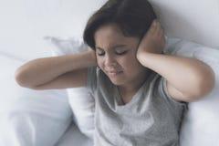 Una pequeña muchacha negro-cabelluda que miente en una cama blanca con sus manos detrás de su cabeza Imágenes de archivo libres de regalías