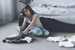 Una pequeña muchacha negro-cabelluda se sienta en el piso y recoge su mochila gris en escuela Fotografía de archivo libre de regalías