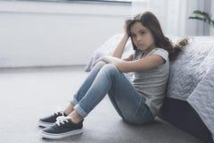 Una pequeña muchacha oscuro-cabelluda se sienta en el piso que se inclina en la cama y que apoya su cabeza con su mano Foto de archivo libre de regalías
