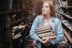 Una pequeña muchacha que se coloca en una librería vieja grande y que sostiene muchos libros en sus manos Ella está buscando para Imágenes de archivo libres de regalías