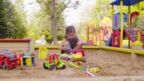 Una pequeña muchacha que se sienta en una salvadera está cogiendo la arena almacen de video