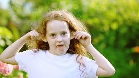 Una pequeña muchacha rizada en una camiseta blanca es sonrisa, enojado, caprichoso, mostrando un puño en el parque en el verano almacen de metraje de vídeo