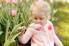 Una pequeña muchacha rubia con los ojos azules se está sentando en la hierba y el s foto de archivo libre de regalías