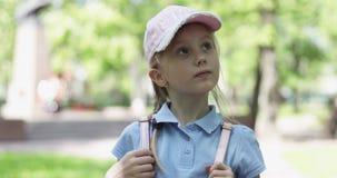 Una pequeña muchacha rubia linda en un casquillo y pantalones cortos está caminando en el parque almacen de video