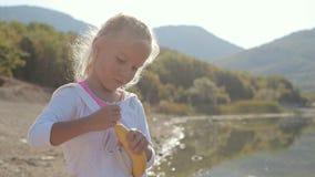 Una pequeña muchacha rubia linda que se coloca en la orilla de almacen de metraje de vídeo