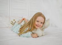 Una pequeña muchacha rubia miente en cama y abraza un oso Muchacha en pijamas, cama blanca imagenes de archivo