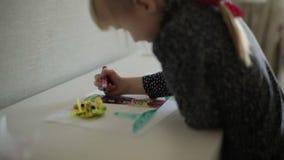 Una pequeña muchacha rubia que dibuja dos imágenes al mismo tiempo Cámara lenta metrajes