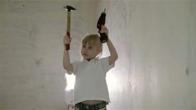 Una pequeña muchacha rubia que muestra un martillo y un taladro al mismo tiempo almacen de video