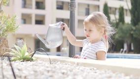 Una pequeña muchacha rubia riega suavemente una flor en la calle metrajes