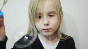 Una pequeña muchacha rubia sopla una burbuja de aire grande almacen de video