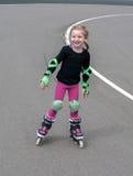 Una pequeña muchacha sonriente que practica en línea (rodillo) el patinar en el estadio al aire libre foto de archivo libre de regalías