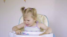 Una pequeña niña dulce está llorando Los rasgones fluyen abajo de sus mejillas Bebé gritador encantador almacen de video