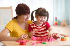 Una pequeña niña linda y su mamá que juegan con la arena cinética en casa Imágenes de archivo libres de regalías