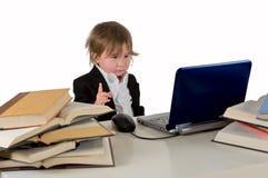 Una pequeña niña (muchacho) que trabaja en el ordenador. Imagen de archivo