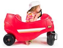 Una pequeña niña que juega con el coche del juguete. Foto de archivo libre de regalías