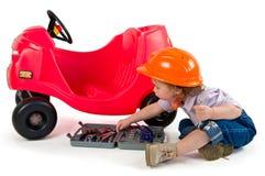 Una pequeña niña que juega con el coche del juguete. Imagenes de archivo