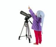 Una pequeña niña que mira con alcance y pointin de la localización Fotografía de archivo libre de regalías