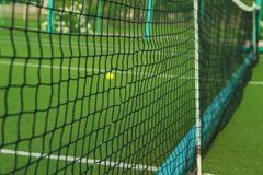 Una pequeña pelota de tenis verde miente detrás de la rejilla Foto de archivo