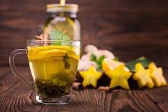 Una pequeña taza llena de té verde del limón en un fondo de madera oscuro Una taza de té dulce al lado del carambola, del jengibr Imagen de archivo libre de regalías