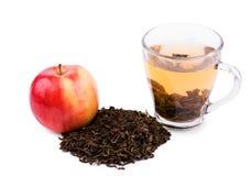 Una pequeña taza llena de té verde Una taza de té hermosa cerca a las hojas maduras enteras de un andtea de la manzana, aisladas  Imagen de archivo libre de regalías