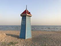 Una pequeña torre en los colores azules y rojos de la playa del mar imagenes de archivo