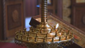 Una pequeña vela en una palmatoria de la iglesia